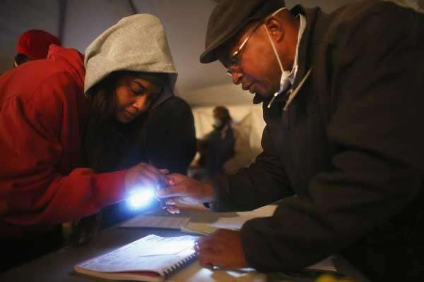 Sheresa Walker, left, uses a flashlight before voting