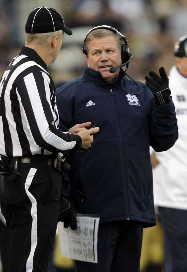 Notre Dame head coach Brian Kelly, right, questions