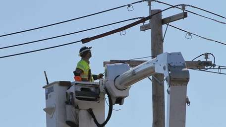 A utility worker works on an overhead line