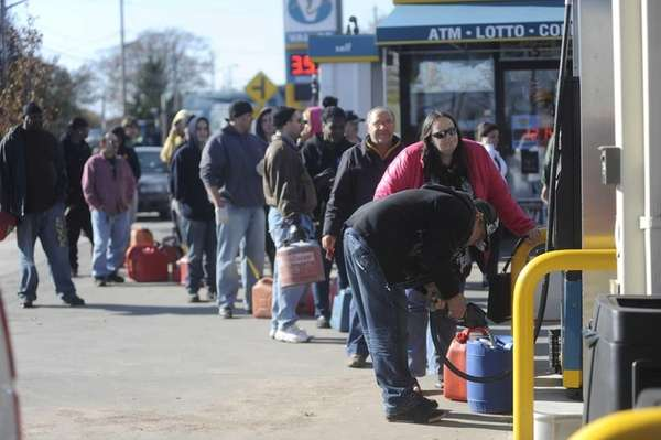 People line up with gas containers to gas