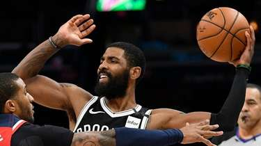 Nets guard Kyrie Irving looks to pass as