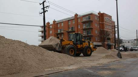 Sand is moved from West Broadway in Long