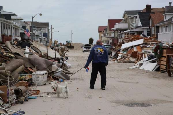 A man walks his dog among the devastation
