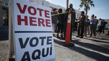 People wait in line to vote on the