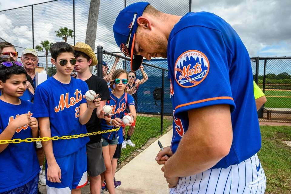 Mets outfielder Brandon Nimmo signs autographs during a