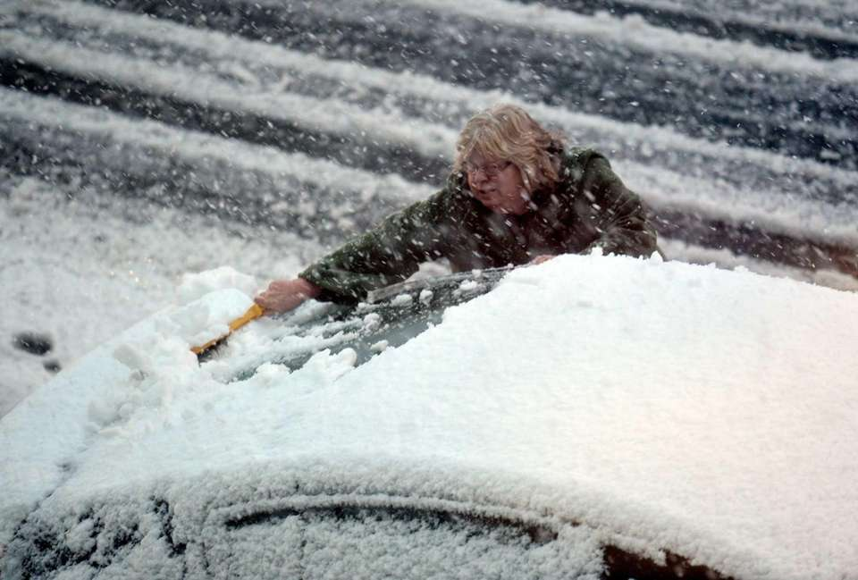 A woman clears snow from the windows of