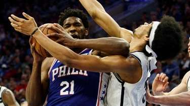 The 76ers' Joel Embiid, left, commits a flagrant