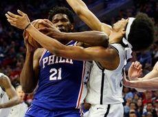 The 76ers' Joel Embiid, left, commits a flagrant
