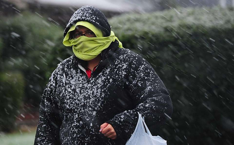 Pedestrians deal with snow, rain and high winds