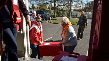 Volunteers with the American Red Cross load containers