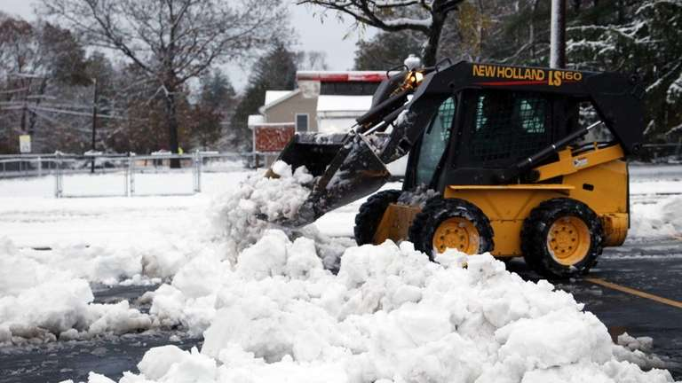 A worker removes snow from a parking lot