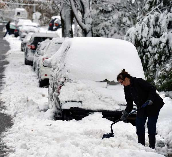 A woman shovels snow on Grant Avenue in