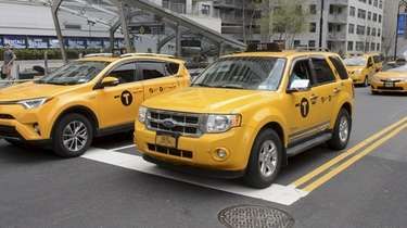 Yellow cabs travel along East 86th Street in