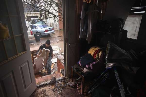 Eddie Saman clears out destroyed household belongings from