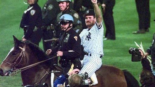 Then-Yankees third baseman Wade Boggs rides a police