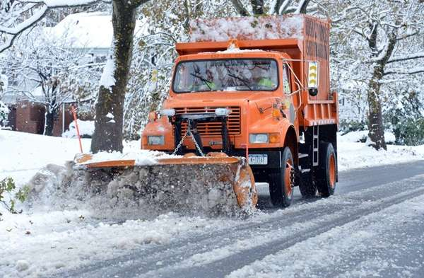 A snow plow clears Newmarket Road from the