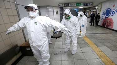 Workers wearing protective gears help clean each other's