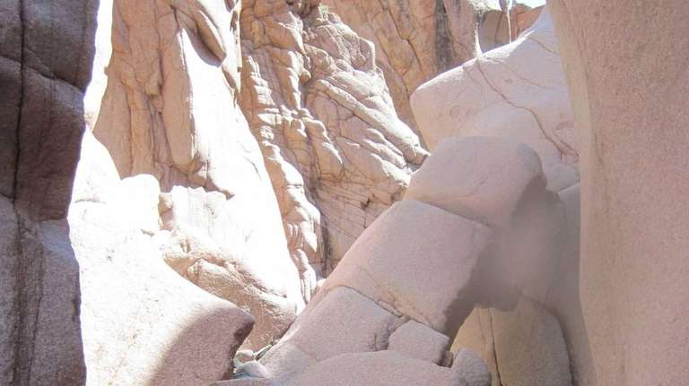 Hikers in wetsuits and helmets wading in Salome