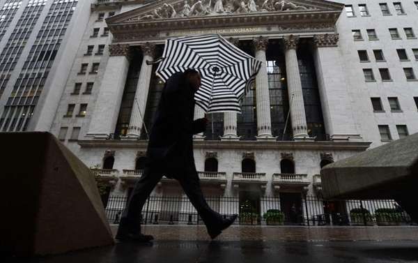 A pedestrian walks past the New York Stock