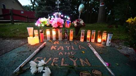 Candles are lit near the site where Evelyn