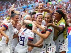 Megan Rapinoe celebrates with teammates after scoring her