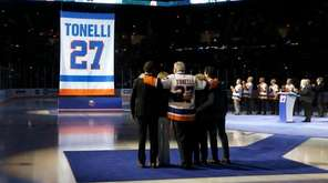 Former Islander John Tonelli stands with his family