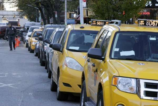 A line of cars, including several taxi cabs,