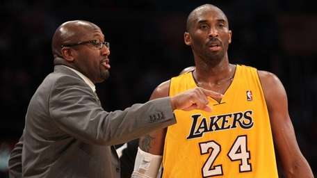 Kobe Bryant of the Los Angeles Lakers confers
