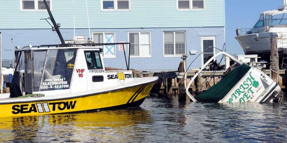 A Sea Tow operator inspects one of damaged