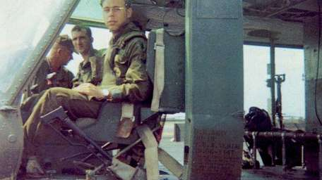 Specialist Rick Serynek in a helicopter during his