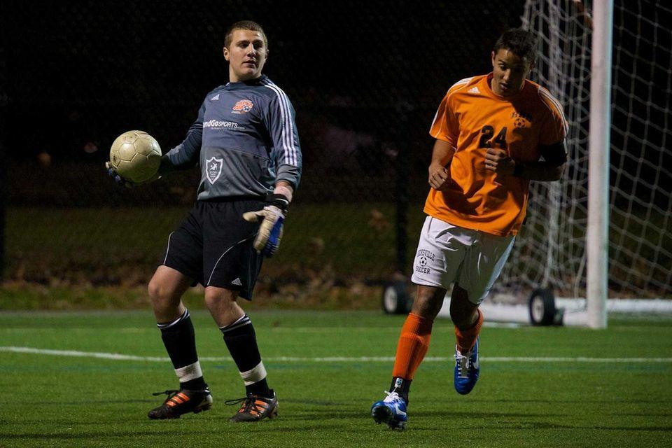Massapequa goalie Dan Vitiello looks to pass the