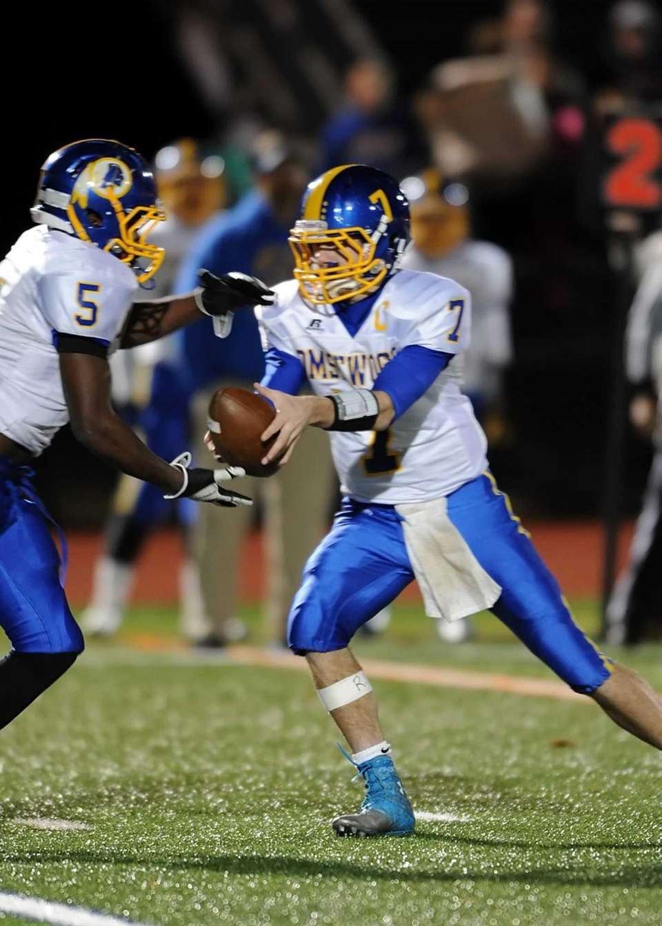 Comsewogue quarterback Ryan Keefe hands off to Ade