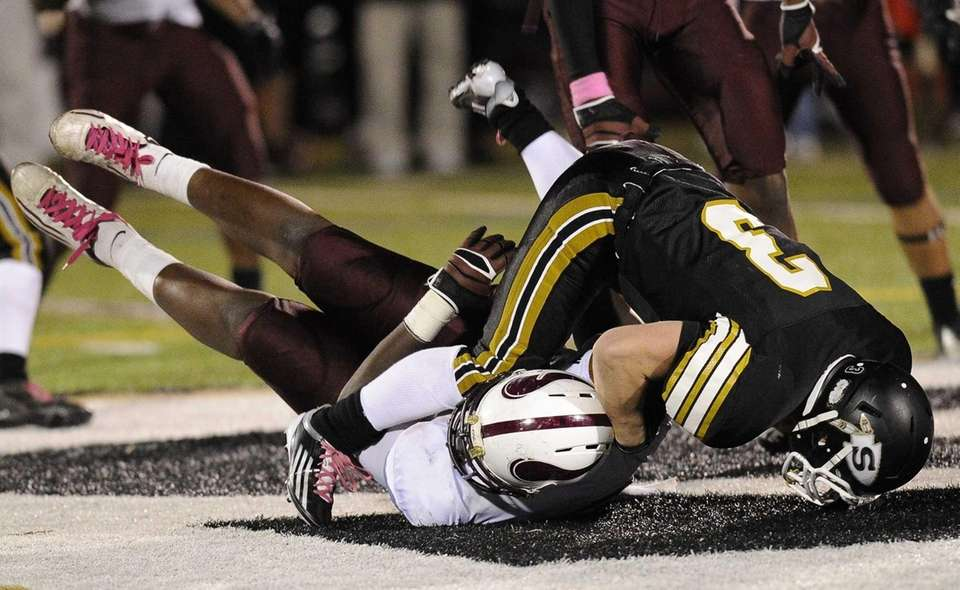Sachem North's Kevin Lathan is brought down by