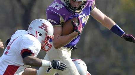 Sayville's John Haggart leaps over Amityville defenders during