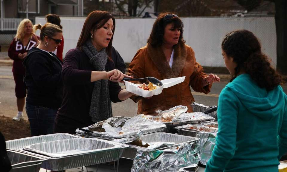 Volunteers load trays full of food on South