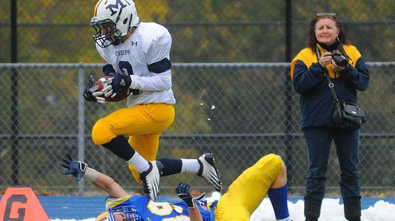 Massapequa High School wide receiver Harry Lowe evades