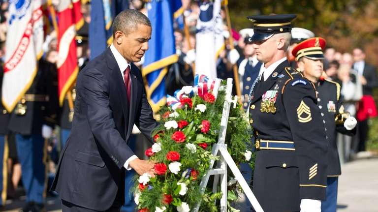 President Barack Obama lays a wreath during a