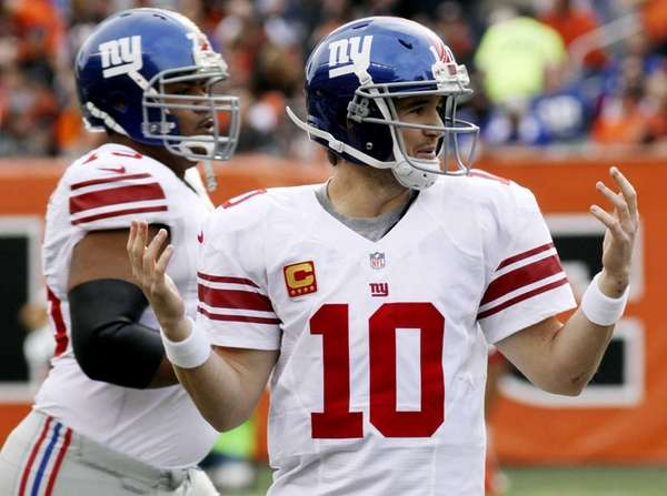 Giants quarterback Eli Manning holds up his hands