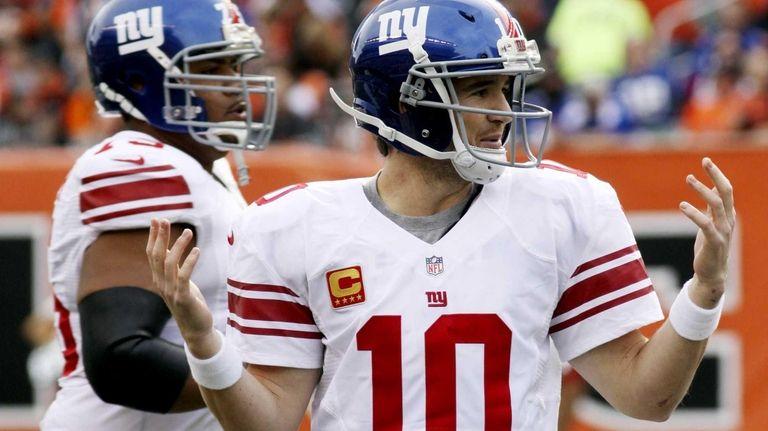 Giants quarterback Eli Manning holds up his hands