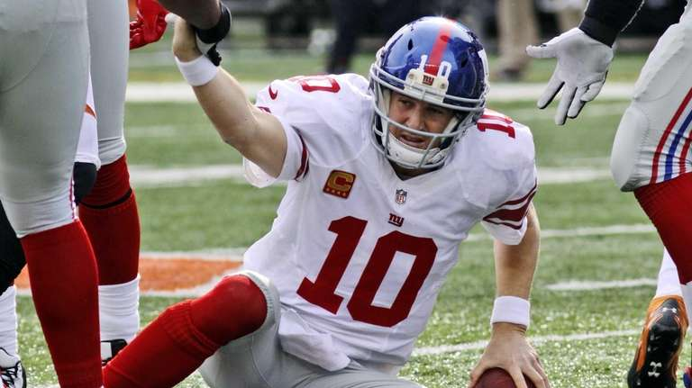 New York Giants quarterback Eli Manning is helped