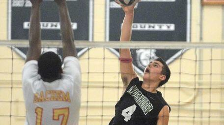 Lindenhurst's Mike Comens spikes the ball while Sachem
