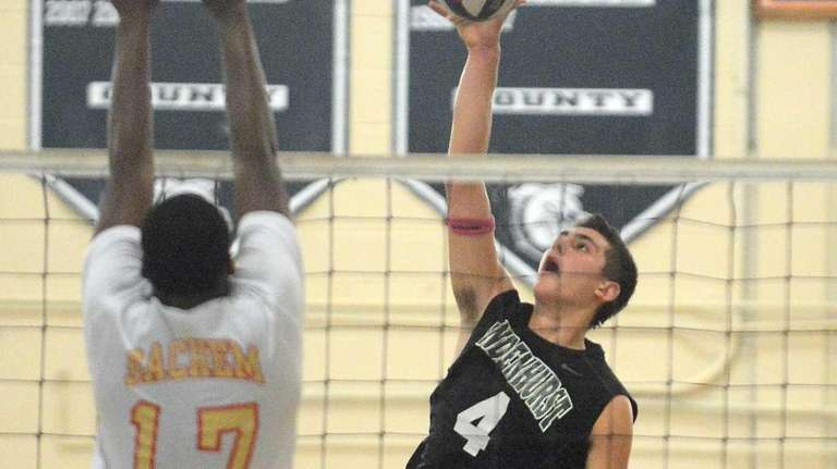 Lindenhurst's Mike Comens spikes the ball while Sachem
