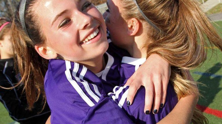 Islip's Kerri McDonald, left, is embraced by teammate