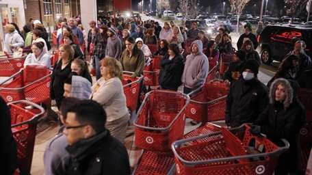A crowd of shoppers wait outside the Target
