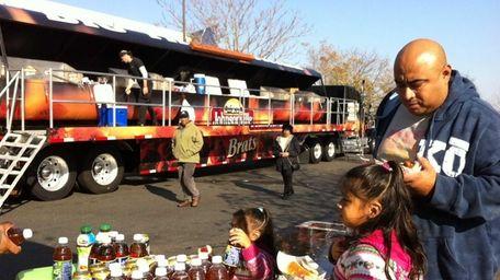 Eddie Chavez, of Freeport, enjoys free bratwurst from