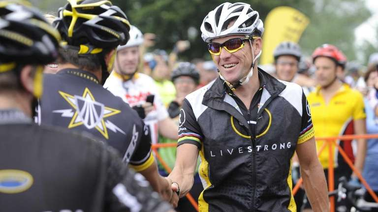 This file photo shows Lance Armstrong, center, greeting