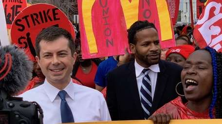Democratic presidential candidate Pete Buttigieg marches outside a