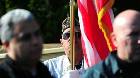 Vietnam veteran Howard Kalachman holds the American flag
