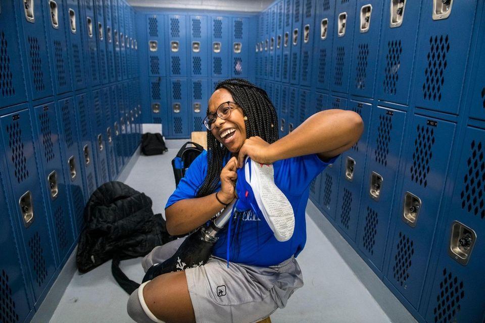 Amaya Williams puts on sneakers on her prosthetics