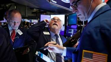 Traders Michael Urkonis, left, and Peter Tuchman, center,
